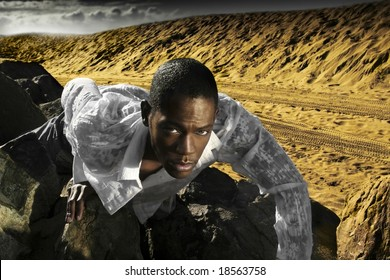 young man crawling on desert rocks with clouds in background