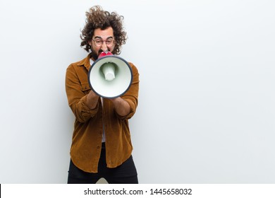 young man with crazy hair in motion shouting and holding a megaphone