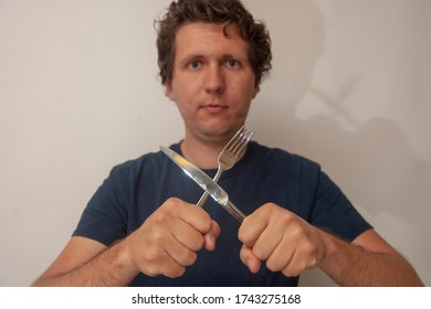 Young man with crossed fork and knife. Concept of ready to eat, hungry, delicious.