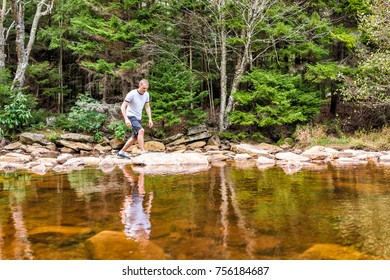 Young man crossing peaceful, calm Red Creek river in Dolly Sods, West Virginia during sunny day with reflection