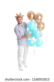 Young man with crown and air balloons on white background