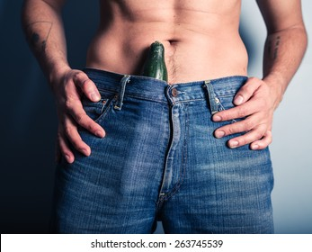 A young man with a cucumber stuffed down his pants