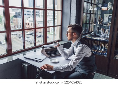 Young man with a cup of coffee in the office