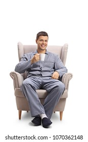 Young man with a cup sitting in an armchair isolated on white background