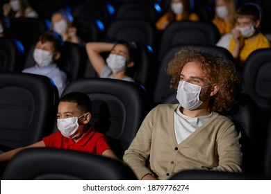 Young man with curly hair enjoying time with little half african brohter during world pandemic. Selective focus of boy watching cartoon in cinema, wearing white face masks, social distancing.