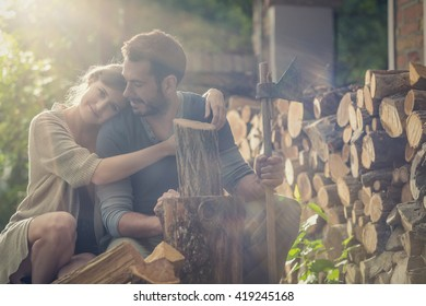 Young man cut wood with girlfriend in the garden
