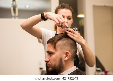 young man cuts hair in the beautiful barber shop