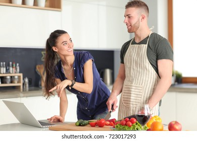 Young man cutting vegetables and woman standing with laptop in the kitchen