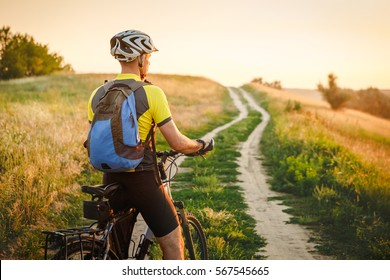 Young man cycling on a rural road through sunset summer meadow