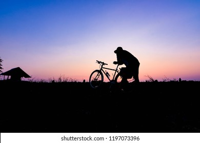 Young man cycling on a sloping hill in the evening.