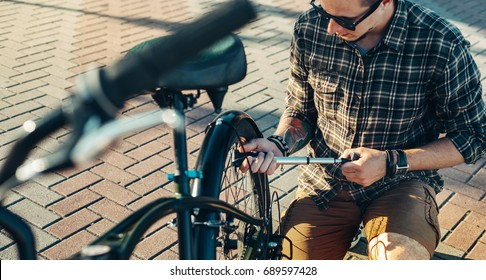 Young Man Cyclist  Pumping Wheel Bike, Preparing For Trip, Maintenance Transport Concept