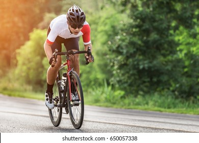 Young man Cyclist riding a bike on an open road to the sunset.