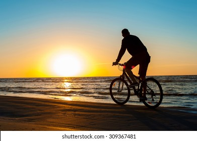 Young man cyclist silhouette on blue sky and sunset background on the beach. Summertime multicolored outdoors horizontal image.