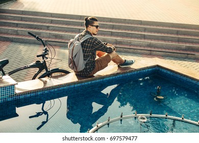 Young Man Cyclist Sitting Near Fountain Next To Bicycle In Summer Park Daily Lifestyle Urban Resting Concept