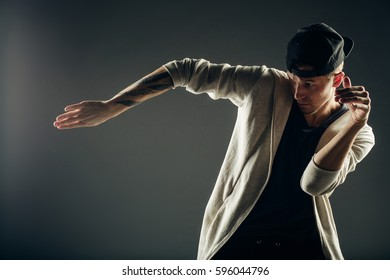 Young man dancer. On grey background.