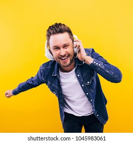 young man dancing and listening music. emotions, facial expressions, feelings, body language, signs. image on a yellow studio background.