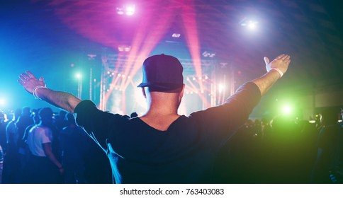 Young man dancing in night club festival event party with laser lights and dj playing in background - Happy people having fun inside disco  - Nightlife and music entertainment concept - Focus on hat
