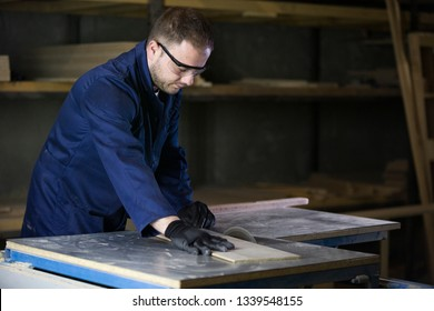 A young man in a dark coat cut the wooden pieces for the sofa on a cutting machine. In front of him on a wall there are a lot of tools and materials. He is wearing a safety glasses and gloves.