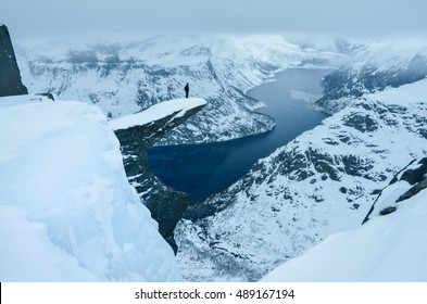 Young man in dark colors standing on famous trolltunga rock and looking at wonderful winter landscape. Original touristic wallpaper.