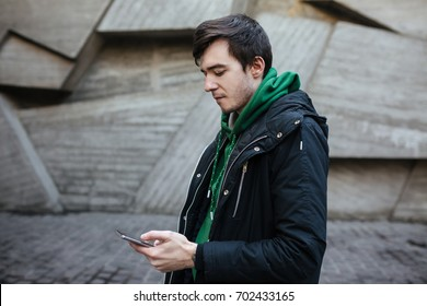 Young man with dark hair in black jacket standing on street with mobile phone in hands. Thoughtful boy in green sweatshirt standing outside and seriously looking in his cellphone