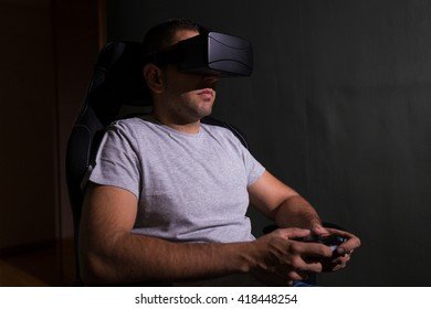 Young man in a dark room wearing virtual reality glasses and playing a videogame using a remote controler.