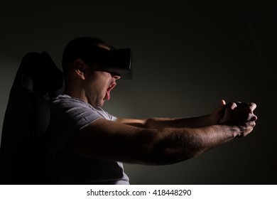Young man in a dark room wearing virtual reality glasses and playing a videogame. Game addiction concept