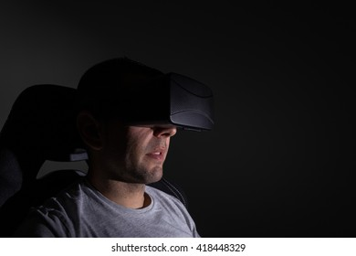 Young man in a dark room wearing virtual reality glasses.