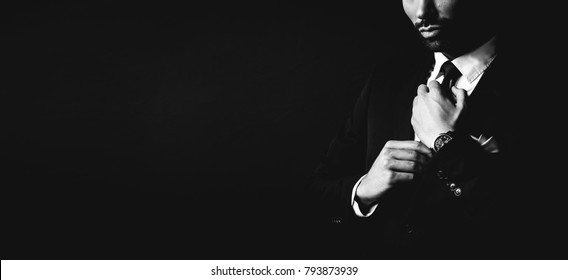Young man in dark suit fixing his tie. Businessman. Black and white portrait.