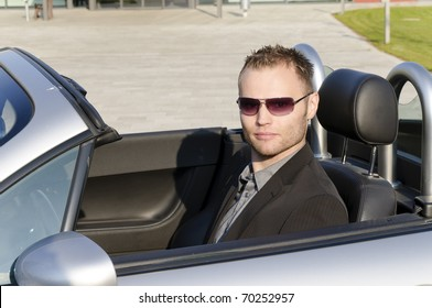 Young man in a dark suit and sunglasses, driving in his open sports car and is very relaxed.