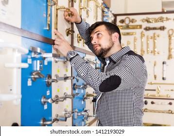 Young man deciding on best door handle in houseware store