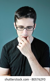 A young man in deep thought with his hand to his chin.