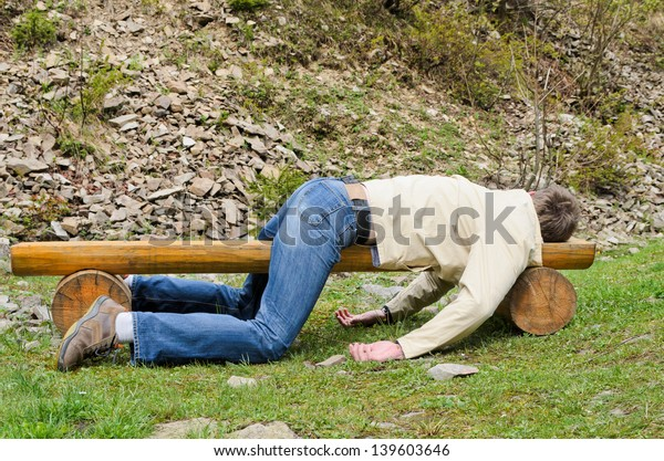 Young man deeply sleeping or drunk, laying outdoors on a wooden park bench. Profile view