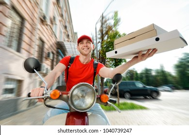 Young man is delivering online orders, driving a motorcycle. Fast food, fresh Italian pizza. Express delivery concept.
