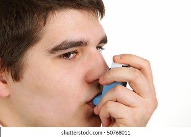 Young man demonstrates the use of an asthma or bronchial inhaler.