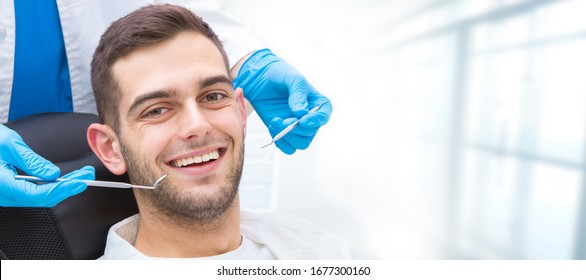 young man in the dental clinic with tools and hands of the dentist