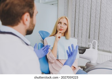 Young man dentist doctor wear white gown talk speak with patient consult minded wistful woman prop up chin sit at dentist office chair indoor cabinet near stomatologist Healthcare enamel treatment.
