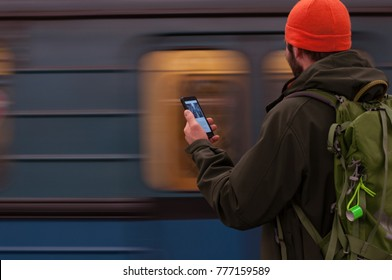 A young man at a departing train on an apron in the subway, the train departs (blurred)