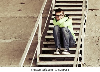 Young man in depression sitting on the steps