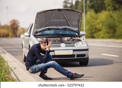 A young man in despair clutched his head, because his car broke down on the road and it is not possible to repair it.