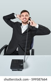 young man dials the phone number while sitting in the office