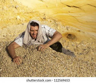 Young man digging in sand