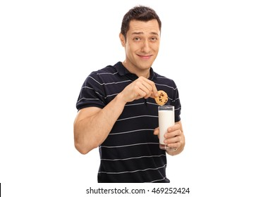 Young man dipping a cookie in a glass of milk isolated on white background
