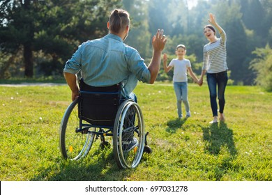 Young man with disabilities waving hello to his family