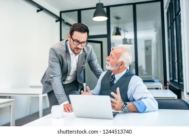 Young man discussing with boss or older employee in modern office.