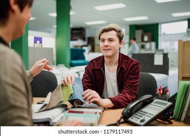 Young man is discussing fabric swatches with a sales clerk in a furniture shop.