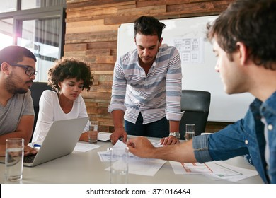 Young man discussing market research with colleagues in a meeting. Team of young professionals having a meeting in conference room looking at documents.