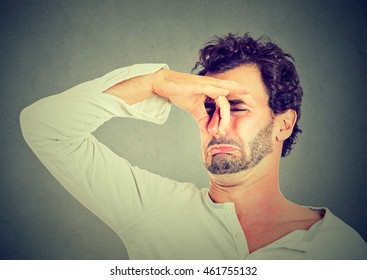 young man with disgust on his face pinches nose, something stinks, very bad smell isolated on gray background. Negative emotion facial expression