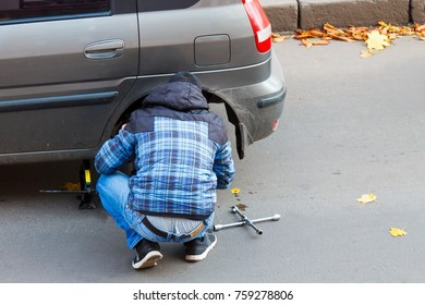 A young man dismount a damaged wheel of his car.