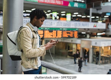 Young man at the display with the phone and backpack looking at camera.