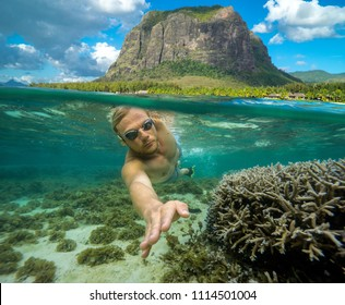 A young man dives among the multicolored corals in the Indian Ocean. Snorkeling in Mauritius. At the top of the picture there is a high mountain